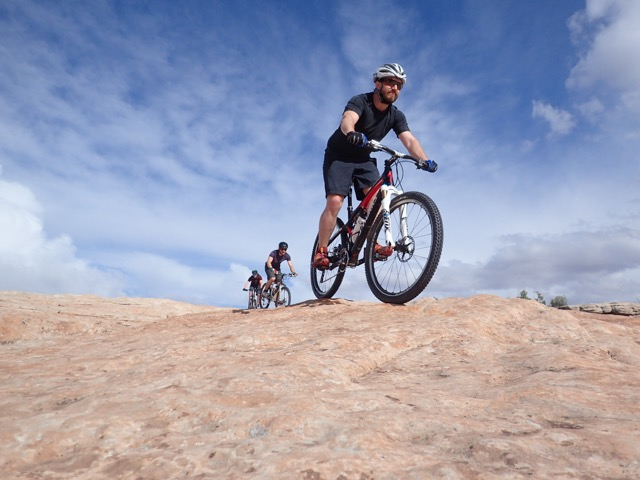 a mountain biker rolling over slip rock in Utah